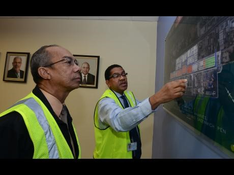 CEO of Kingston Wharves Limited Grantley Stephenson (right) explains a map of the port facility to minister without portfolio in the Ministry of Economic Growth and Job Creation, Dr Horace Chang, during a tour of Kingston Wharves on Thursday, October 27.